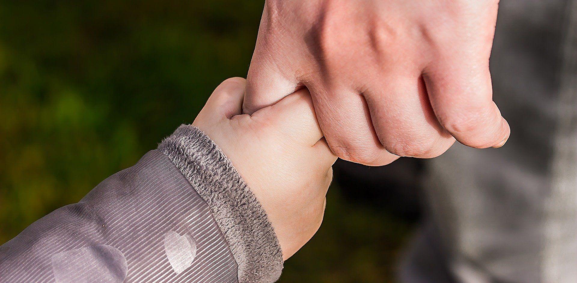 Kind und Erwachsener halten Hände