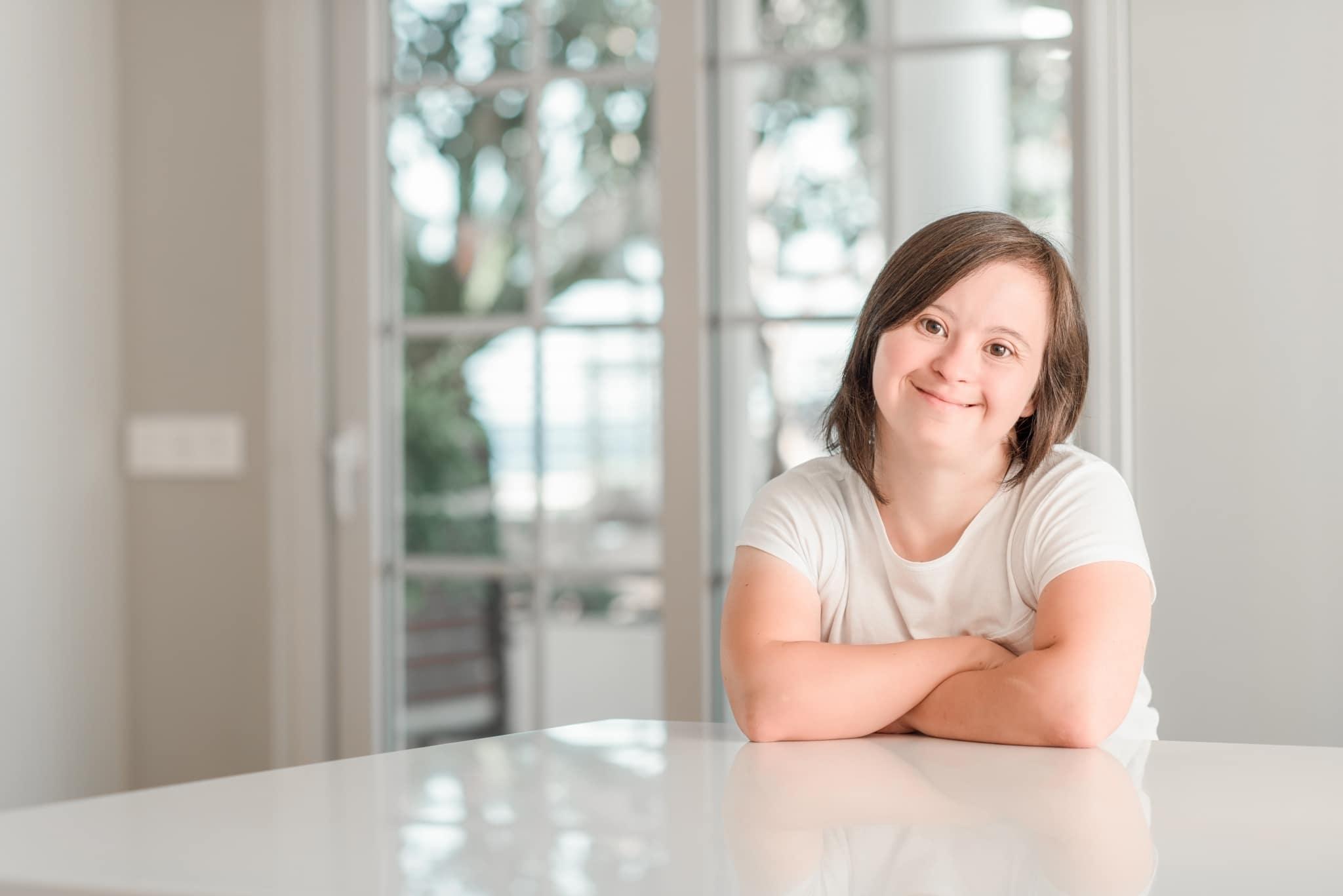 Fröhliches Mädchen sitzt am Küchentisch