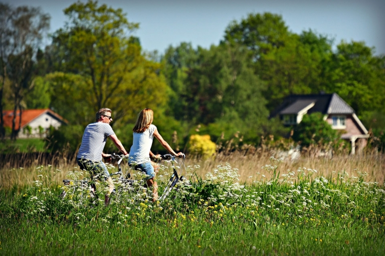 Mann und Frau fahren mit dem Rad durch Feld