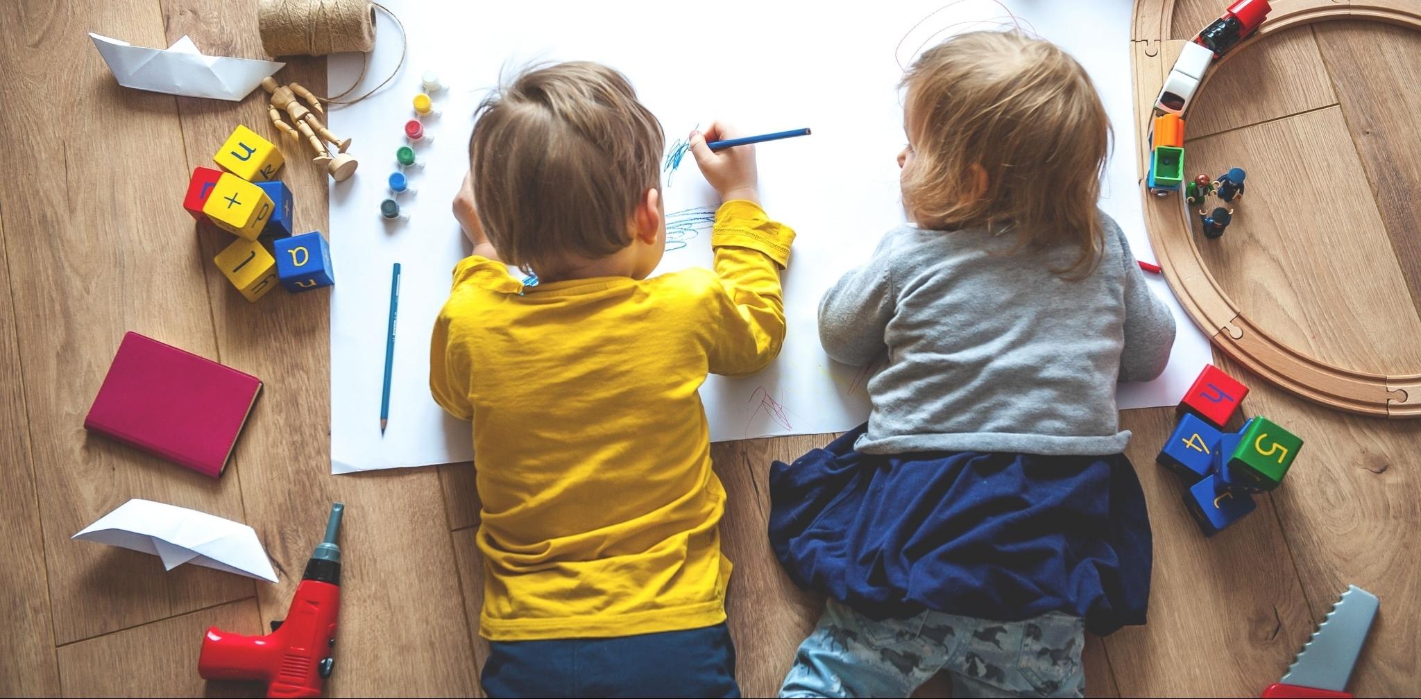 Kinder zeichnen am Boden
